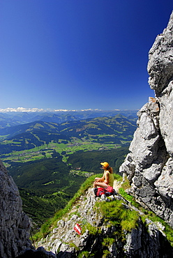 hiker at notch Kleines Toerl with view to the valley of Ellmau and Going, Hohe Tauern in background, Kaiser range, Tyrol, Austria
