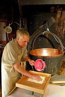 alpine cowboy making cheese in front of copper kettle, Ranggenalm, Kaiser range, Tyrol, Austria