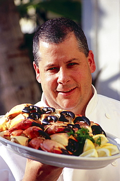 Chef with plate of stone crabs, Restaurant Joe's Stone Crab, South Beach, Miami, Florida, USA