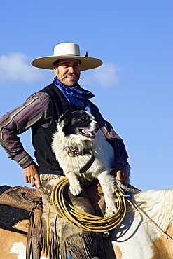 cowboy sitting on horseback with dog, wildwest, Oregon, USA