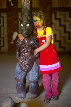 Girl with facepainting (like a Maori Moko - Tatoo), wooden Maori sculpture in Marae, celebrations on Waitangi Day, Okains Bay Museum, Bank`s Peninsula, east coast, South Island, New Zealand