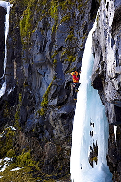 Ice climber on frozen waterfall, Iceland