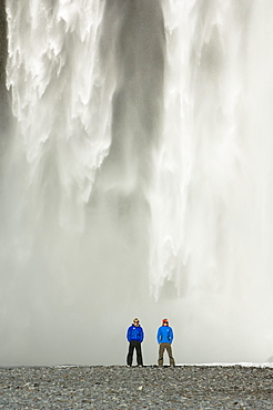 Two men stood in front of a waterfall, Iceland
