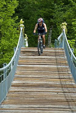 Mountainbiker on suspension bridge, Slovenia
