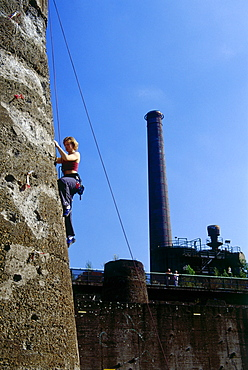Climber climbing up a tower at Huette Meiderich, Public Park in Duisburg North, Duisburg, Ruhr Valley, North Rhine Westphalia, Germany