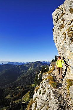 Woman walking on an exposed trail at a rockface, Brunnstein, Bavarian Prealps, Upper Bavaria, Bavaria, Germany