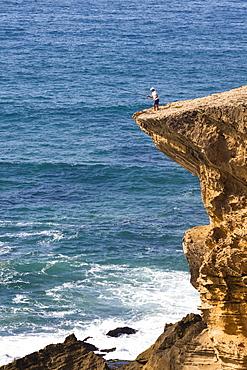 Fisherman on cliff at Monte Clerigo Beach, Atlantic Coast, Algarve, Portugal, Europe