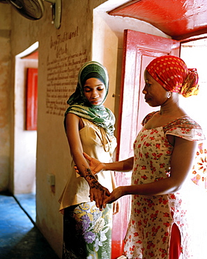 Therapist Acha with client shows henna painting at Mrembo Spa, Mrembo means beautiful woman, old house in the center of Stone Town, Zanzibar, Tanzania, East Africa