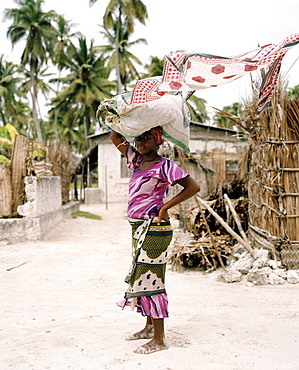 Young woman in traditional cloth Kanga is carrying seaweed, Jambiani, Zanzibar, Tanzania, East Africa