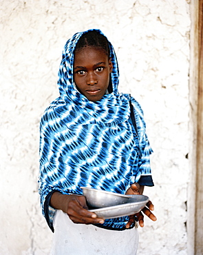 Girl with blue Kanga cloth in front of coral stone house, Jambiani village, Zanzibar, Tanzania, East Africa
