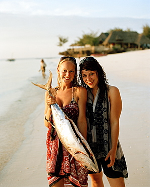 Tourists with bought Yellowtail Tuna for a birthday party, Nungwi, Zanzibar, Tanzania, East Africa