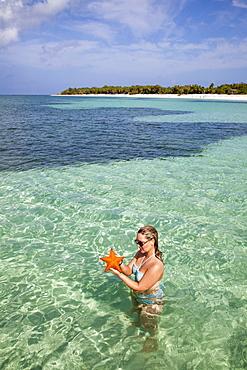 Young woman holding a red starfish in shallow water at Punta Frances Parque Nacional, Isla de la Juventud, Cuba, Caribbean