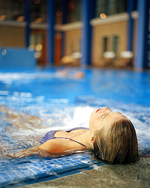 Woman lying in a swimming pool in a spa resort, Travemuende, Luebeck, Schleswig-Holstein, Germany