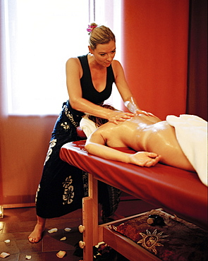 Woman enjoying traditional Hawaiian massage Lomi Lomi Nui in a spa resort, Travemuende, Luebeck, Schleswig-Holstein, Germany