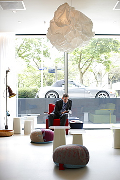 Guest in the Lobby with designer furniture, Citizen M Hotel, Amsterdam, Netherlands