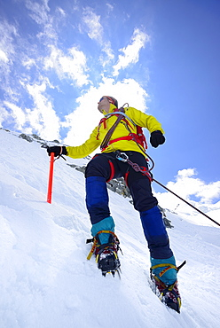 Mountaineer ascending with crampons and ice axe, Piz Palue, Grisons, Switzerland