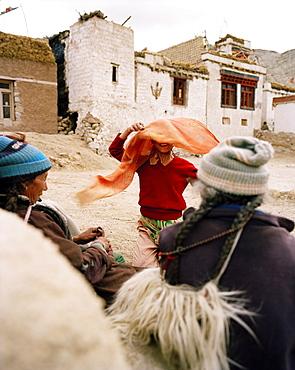 Girl banters with women in village Yangthang, Sham Trek west of Leh, Ladakh, Jammu and Kashmir, India