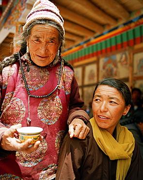 Women drinking tea in the courtyard, Hemis Festival at convent Hemis, southeast of Leh, Ladakh, Jammu and Kashmir, India