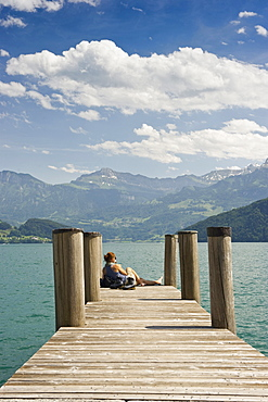 Female hiker sitting on a landing stage in Weggis, Lake Lucerne, canton Lucerne, Switzerland, Europe