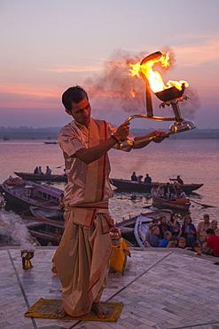Hindu monk performs prayer ceremony at Dasaswamedh Ghat alongside Ganges river at sunrise, Varanasi, Uttar Pradesh, India
