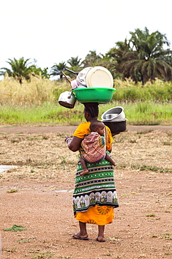 Local woman carrying baby and dishes to the lake to wash up, lake Tanganyika, Mahale Mountains National Park, Tanzania, East Africa, Africa