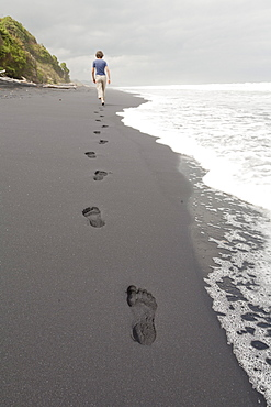 Footprints in black sand, woman walking along the beach, South Island, New Zealand