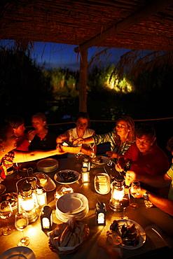 Guests having dinner on the wooden deck at night, Hotel Areias do Seixo, Povoa de Penafirme, A-dos-Cunhados, Costa de Prata, Portugal