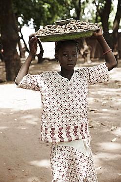 Girl carrying on head a tray with peanuts to market, Yanfolila, Sikasso Region, Mali