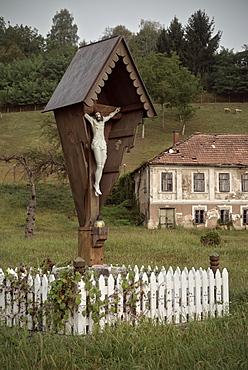 Jesus at cross in front of deserted house, rural Krsko, Dolenjska, Bela Krajina, Slovenia