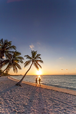 Morning impression with couple jogging along the beach at sunrise, Key West Smathers Beach, Key West, Florida Keys, Florida, USA