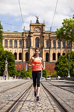 Young woman jogging over Maximilian bridge, Maximilianeum in background, Munich, Bavaria, Germany