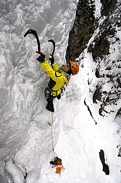 Young woman ice climbing, Engadin, Grissons, Switzerland, Europa