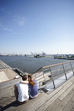 Couple on the terrace of Dockland, office building, near Altona fishing harbour, Hamburg, Germany