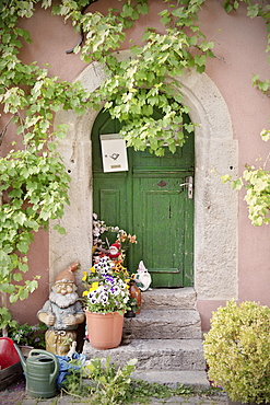 Decorated front door with flowers and garden gnome, Rothenburg ob der Tauber, Romantic Road, Franconia, Bavaria, Germany