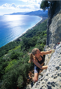 Young woman climbing on rockface, Finale, Liguria, Italy