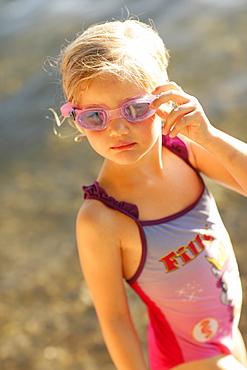 Girl 4 years wearing swimsuit and swim googles at lake Starnberg, Ammerland, Munsing, Upper Bavaria, Germany