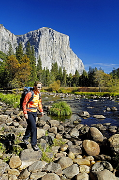 Woman wearing rucksack hiking on stony brookside, Yosemite National Park, California, North America, America