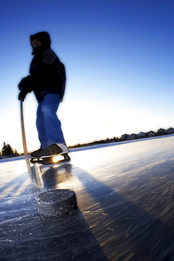 Boy Ice Skating on Lake with Hockey Stick and Puck, Calgary, Alberta
