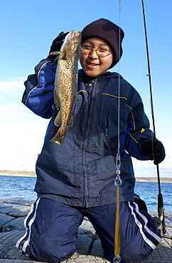 Young boy with freshly caught Arctic Char, Cambridge Bay, Nunavut