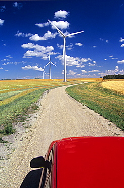 View of a Truck and Wind Turbines on Road through Cropland, near St. Leon, Manitoba