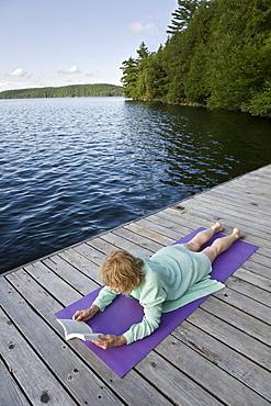Woman reading on cottage dock, Smoke Lake, Algonquin Park, Ontario