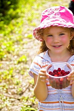 Girl holding container of raspberries, Lincoln Gardens, Lumsden, Saskatchewan