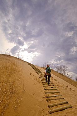 Woman hiking up a sand dune, The Spirit Sands, Spruce Woods Provincial Park, Manitoba