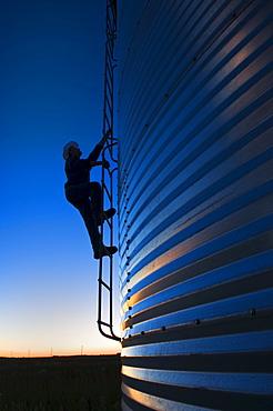 Silhouette of a farmer climbing a grain storage bin, near Carey, Manitoba