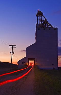 Streak of truck lights and an old grain elevator, Virden, Manitoba