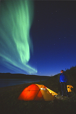 Aurora Borealis above a Tent and Camper along the Peel River, Fort MacPherson, Yukon