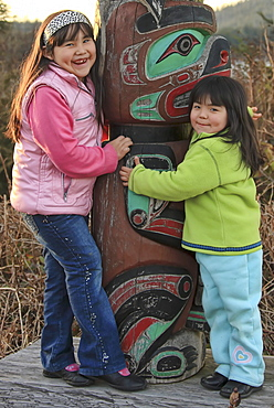 Portrait of young First Nation girls hugging a totem pole, Vancouver Island, British Columbia