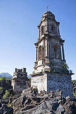 The bell tower of the San Juan Parangaricutiro Church sticks out through the Paricutin Volcano lava flow, Michoacun, Mexico
