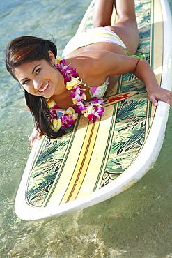 Hawaii, Oahu, Waikiki, Young woman laying on surfboard in water.