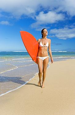 Hawaii, Kauai, Woman walking along beach with beach with surfboard.